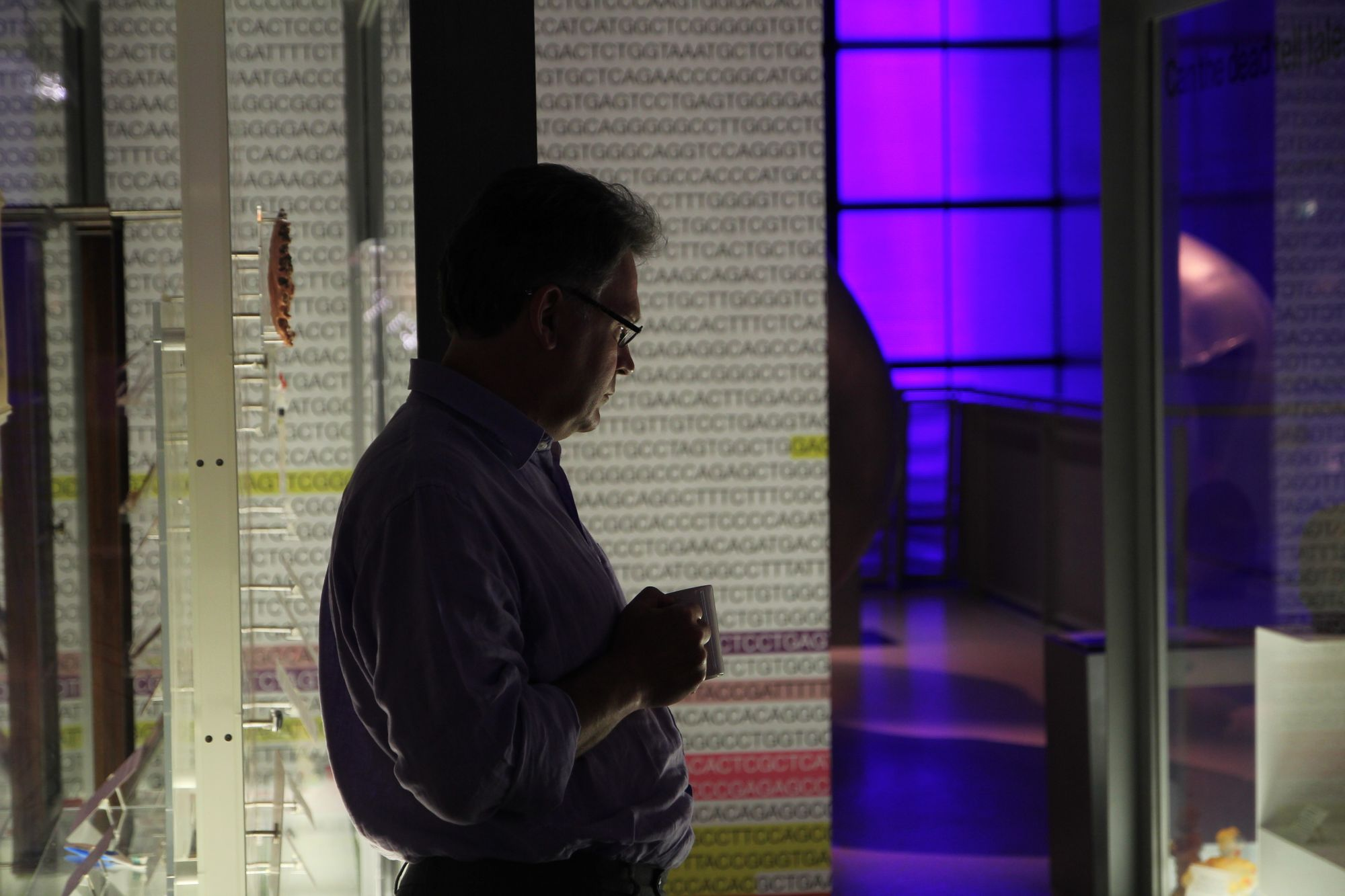 Male person holding a mug looks at a glass exhibition case, with the letters of a DNA sequence in the backdrop