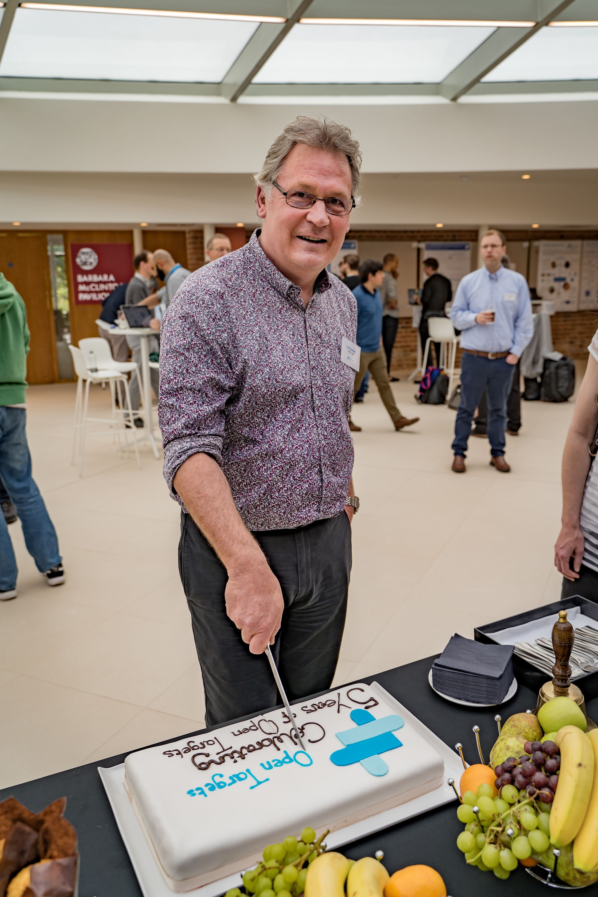 Male person stands behind a table looking at the camera, holding a knife to cut a cake.