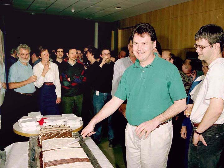 Male person, in a green shirt, stands behind a table smiling at the camera, holding a knife to cut a cake.