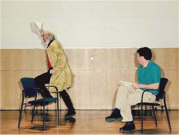 One person stepping onto a chair holding a piece of paper, another person sitting on a chair looking at the first person