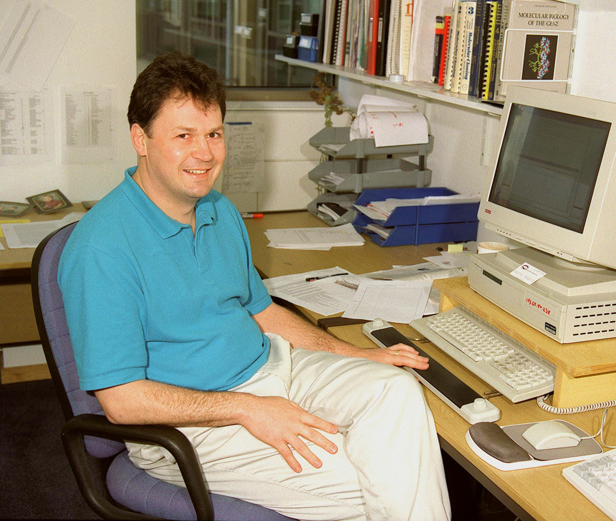 Male person in a blue polo sitting at a desk with a computer and papers, smiling at the camera